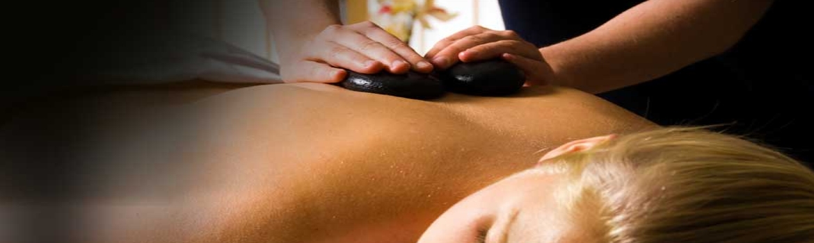 Client relaxes during hot stone massage performed on her middle back.